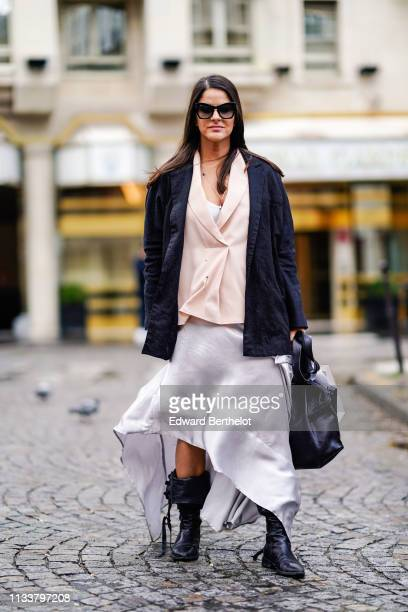 A guest wears sunglasses a pale pink wrapover top a black jacket a black bag a white flowing skirt black boots outside Nobi Talai during Paris...