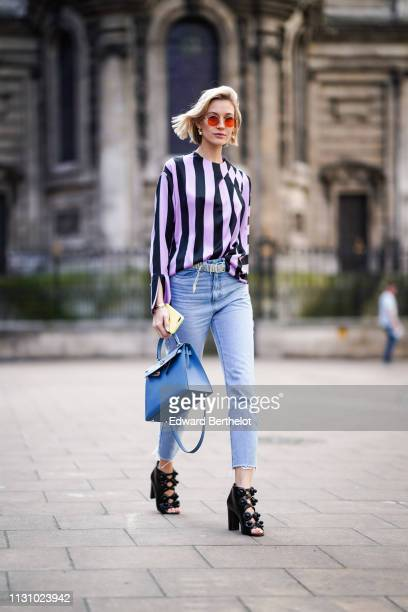 A guest wears sunglasses a pale purple with black stripes top crop ripped jeans a blue handbag a strass belt black Chanel high heels peeptoe pumps...