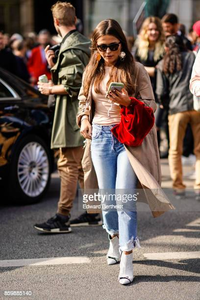 A guest wears sunglasses a peachcolor top a beige trench coat ripped blue jeans white ankle boots with black bows outside the Dries Van Noten show...