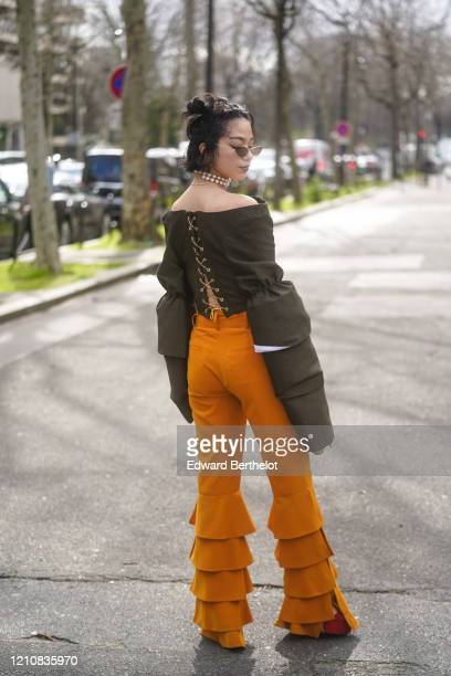 A guest wears sunglasses a pearl necklace/choker a khaki off shoulder top with oversized sleeves orange ruffled flared pants outside Miu Miu during...