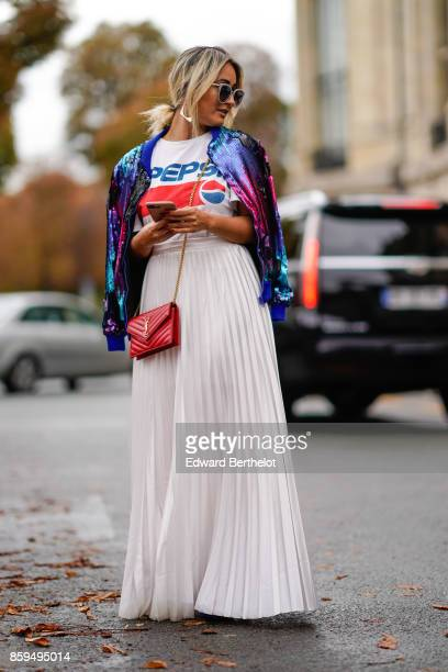 A guest wears sunglasses a Pepsi cola tshirta blue lame shiny jacket a red YSL bag and a long white pleated skirt outside Manish Arora during Paris...
