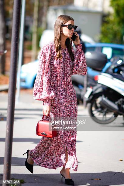A guest wears sunglasses a pink dress a red bag uses a smartphone outside Moncler during Paris Fashion Week Womenswear Spring/Summer 2018 on October...