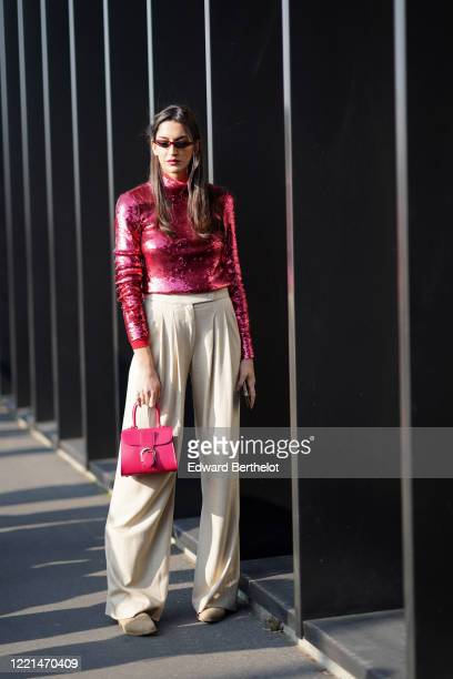 Guest wears sunglasses, a pink glittering shiny top, white flare pants, a pink bag outside Gucci, during Milan Fashion Week Fall/Winter 2020-2021, on...