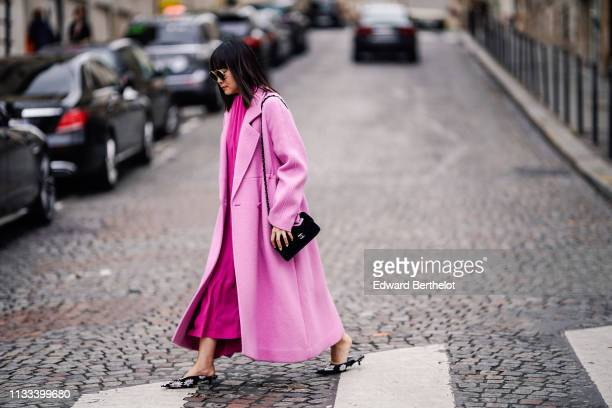 A guest wears sunglasses a pink oversize coat a hot pink pleated dress a Chanel black bag floral print black pointy mules outside Altuzarra during...
