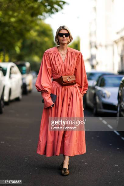 A guest wears sunglasses a pink pleated dress a Chloe brown leather belt bag during London Fashion Week September 2019 on September 14 2019 in London...