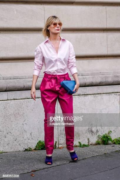 A guest wears sunglasses a pink shirt pink pants a blue triangular bag purple shoes outside Moncler during Paris Fashion Week Womenswear...