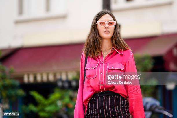 A guest wears sunglasses a pink shirt striped flared pants outside Acne Studios during Paris Fashion Week Womenswear Fall Winter 2019 on July 1 2018...