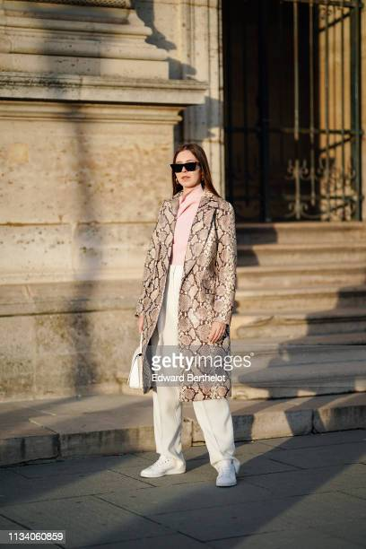 A guest wears sunglasses a pink top a light brown python pattern trench coat white pants white sneakers a white handbag outside Louis Vuitton during...