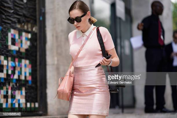 A guest wears sunglasses a pink top a pink glitter skirt a pink bag holds a Canon 1D camera outside Juun J during Paris Fashion Week Menswear...