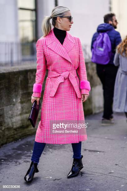 A guest wears sunglasses a pink trench coat a clutch outside Giambattista Valli during Paris Fashion Week Womenswear Fall/Winter 2018/2019 on March 5...