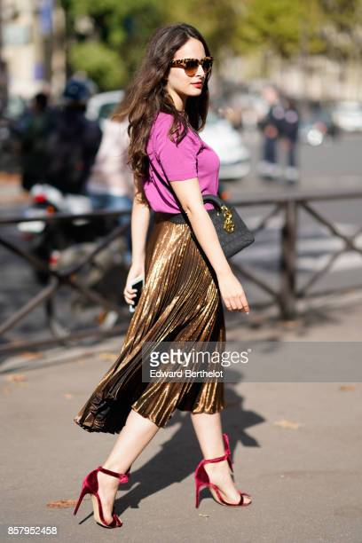 A guest wears sunglasses a pink tshirt a golden pleated shiny skirt red heels shoes outside Miu Miu during Paris Fashion Week Womenswear...
