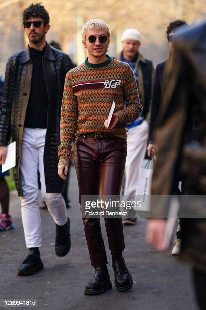 A guest wears sunglasses a Prada pullover with stripes and printed geometric patterns a belt burgundy leather pants leather shoes outside Fendi...
