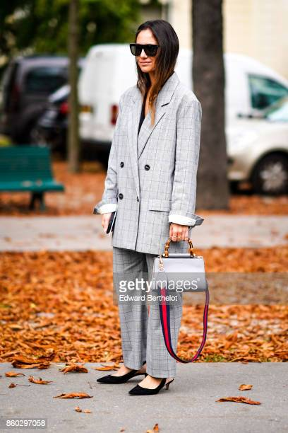 A guest wears sunglasses a Prince of Wales checked oversize doublebreasted pantsuit a grey bag black shoes oversize outside Lanvin during Paris...