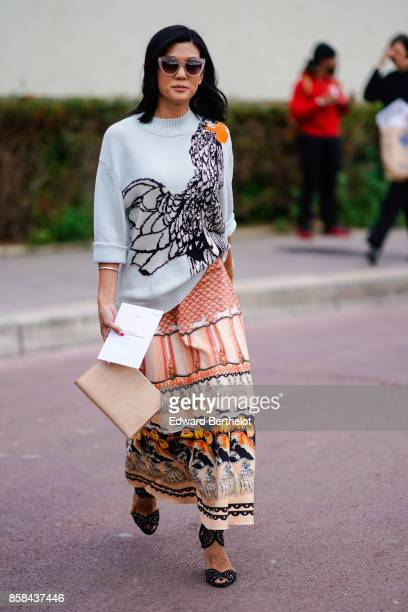 A guest wears sunglasses a pull over with a printed eagle a dress with prints outside Hermes during Paris Fashion Week Womenswear Spring/Summer 2018...