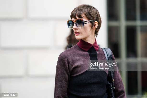 Guest wears sunglasses, a purple and black wool top with burgundy collar, during London Fashion Week Fall Winter 2020, on February 15, 2020 in...