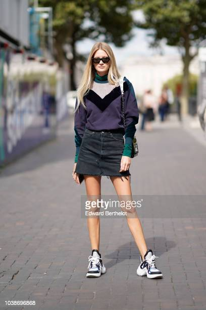 A guest wears sunglasses a purple and green pullover a black denim skirt sneakers during London Fashion Week September 2018 on September 16 2018 in...