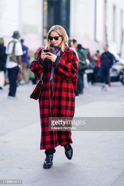 A guest wears sunglasses a purple and white striped shirt with a bow a red and black checkered oversize coat a brown bag black shoes outside Dries...