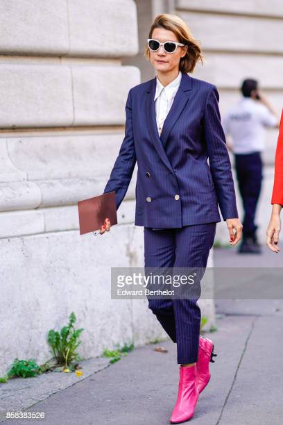 A guest wears sunglasses a purple button blazer jacket purple suit cropped pants pink shoes outside Moncler during Paris Fashion Week Womenswear...
