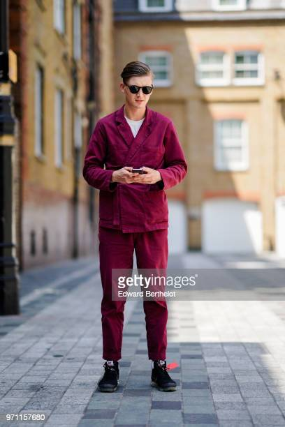 A guest wears sunglasses a purple jacket pants sneakers shoes during London Fashion Week Men's June 2018 on June 10 2018 in London England