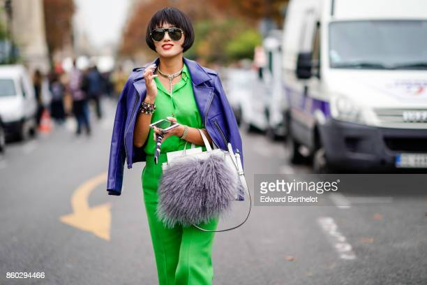 A guest wears sunglasses a purple leather jacket an applegreen pantsuit a white bag with a big grey fur bobble outside Lanvin during Paris Fashion...