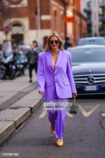 A guest wears sunglasses a purple oversized jacket flowing pants pointy shoes a Valentino bag outside Koche x Pucci during Milan Fashion Week...
