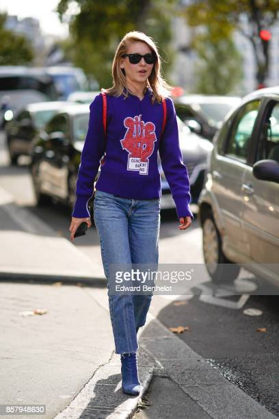 A guest wears sunglasses a purple pull over with an embroidered logo blue jeans blue shoes outside Thom Browne during Paris Fashion Week Womenswear...