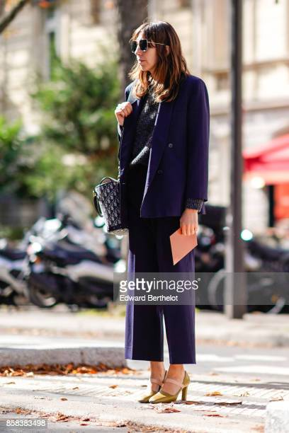 A guest wears sunglasses a purple suit cropped pants golden heels shoes outside Moncler during Paris Fashion Week Womenswear Spring/Summer 2018 on...