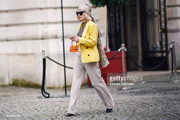 Guest wears sunglasses, a python pattern scarf, a beige and black zebra pattern top, a yellow jacket, a tiny orange Jacquemus handbag, beige flare...