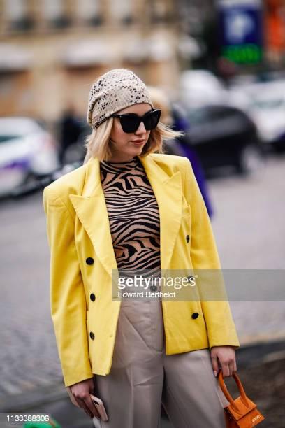 Guest wears sunglasses, a python pattern scarf, a beige and black zebra pattern top, a yellow jacket, a tiny orange Jacquemus handbag, beige pants,...