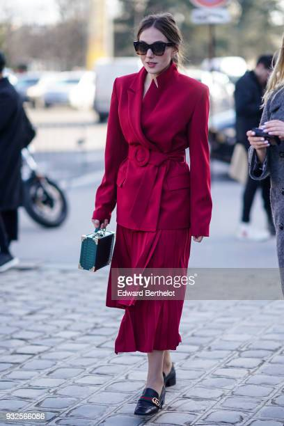 A guest wears sunglasses a raspberry colour suit with a wrap asymmetric pleated midi skirt black moccasins with a red strap a green studded handbag...