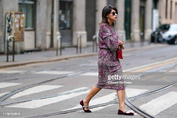Guest wears sunglasses, a red bag, a fuchsia and grey speckled dress, burgundy velvet flat shoes with rhinestone straps, outside the Dolce & Gabbana...
