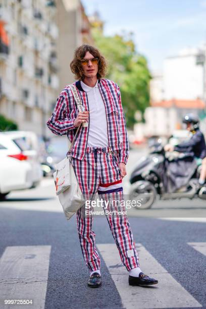 A guest wears sunglasses a red blue and white checked print jacket pants with a printed French flag white socks black shoes outside Wooyoungmi during...