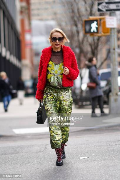 A guest wears sunglasses a red fluffy jacket a mesh top yellow and green military camouflage pants black boots a bag earrings during New York Fashion...