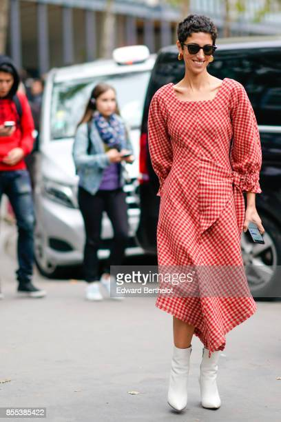 A guest wears sunglasses a red gingham dress white shoes outside Carven during Paris Fashion Week Womenswear Spring/Summer 2018 on September 28 2017...