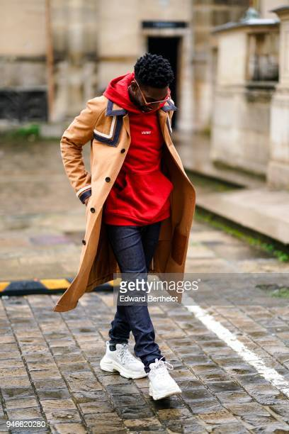 A guest wears sunglasses a red hoodie sweater an orange coat black pants white shoes outside Thom Browne during Paris Fashion Week Menswear Fall...