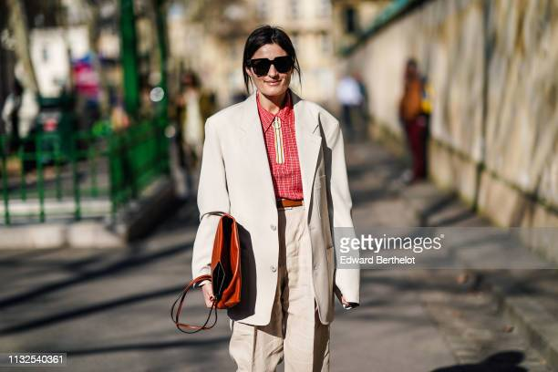 A guest wears sunglasses a red poloshirt a gold leather bag a beige oversize jacket beige linen pants outside Dior during Paris Fashion Week...