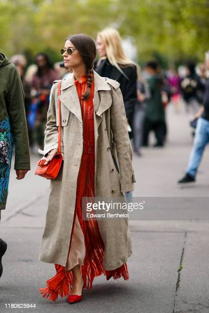 Guest wears sunglasses, a red Valentino bag, a beige linen ripped hem trench coat, a see-through red lace flowing long dress, red suede heels,...