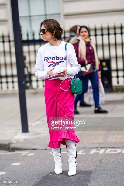A guest wears sunglasses a Reebok logo white pull over a pink pleated skirt white boots a green bag during London Fashion Week February 2018 on...
