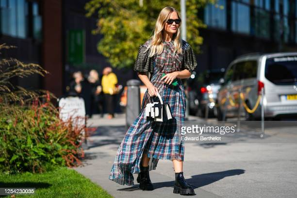 Guest wears sunglasses, a ruffled pleated colored dress with printed checkered and argyle geometric patterns, a black and white leather bag, black...