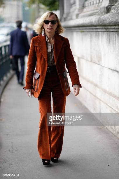 A guest wears sunglasses a rustcoloured pantsuit with flare pants black shoes outside the Dries Van Noten show during Paris Fashion Week Womenswear...