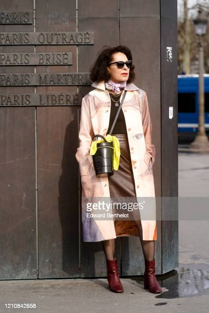Guest wears sunglasses, a scarf, a black leather bag, a trench coat, a brown leather skirt, burgundy leather shoes, a pullover, outside Chanel,...