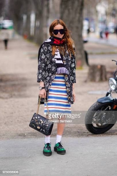 A guest wears sunglasses a scarf a striped dress a Chanel bag green shoes a jacket outside Chanel during Paris Fashion Week Womenswear Fall/Winter...