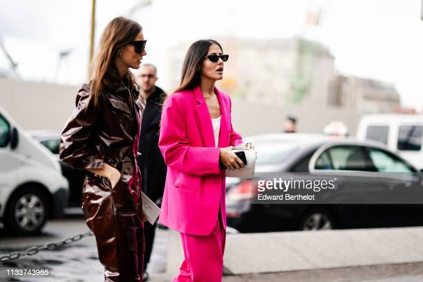 Guest wears sunglasses, a shiny brown jumpsuit ; Gilda Ambrosio wears sunglasses, a white top, a neon pink pantsuit, a white bag, outside...