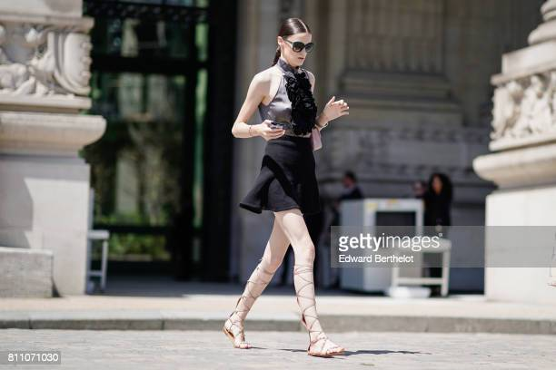 A guest wears sunglasses a silk dress with black embroidery camel lace up flat shoes outside the Chanel show during Paris Fashion Week Haute Couture...