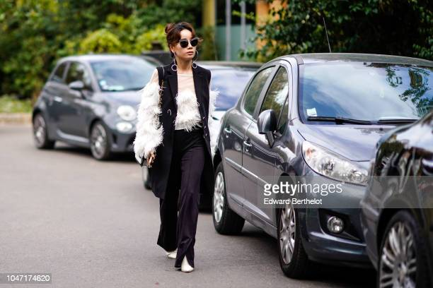 Guest wears sunglasses, a sleeveless jacket, flare pants, white shoes, faux fur, outside Akris, during Paris Fashion Week Womenswear Spring/Summer...