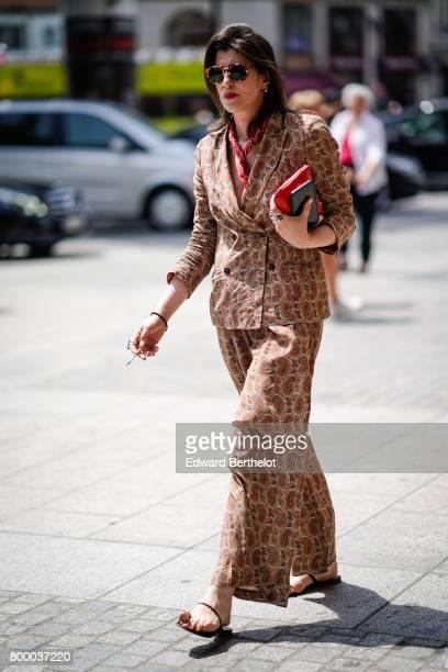 A guest wears sunglasses a snake print blazer jacket snake print pants outside the Louis Vuitton show during Paris Fashion Week Menswear...