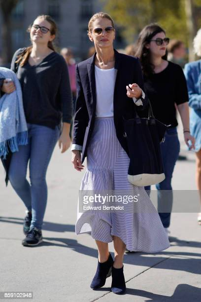 A guest wears sunglasses a striped dress a black blazer jacket outside Nina Ricci during Paris Fashion Week Womenswear Spring/Summer 2018 on...