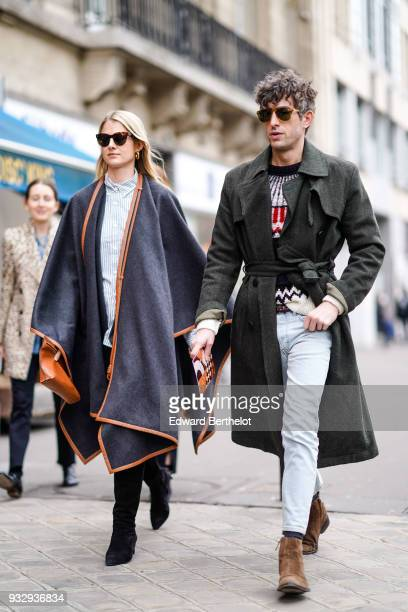 A guest wears sunglasses a striped shirt a grey tawnylined wrap poncho a tawny handbag black boots a guest wears sunglasses a dark green trenchcoat...