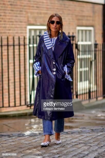 A guest wears sunglasses a striped shirt a purple raincoat blue jeans outside Simone Rocha during London Fashion Week September 2017 on September 16...