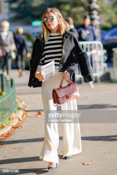 A guest wears sunglasses a striped top a black jacket a pink bag white falre pants outside Chanel during Paris Fashion Week Womenswear Spring/Summer...